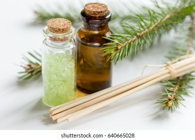 spa with organic spruce oil and sea salt in glass bottles on white table background