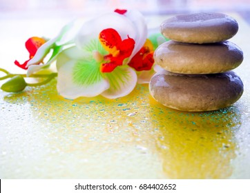 Spa pink orchid with massage stones on blue wooden background