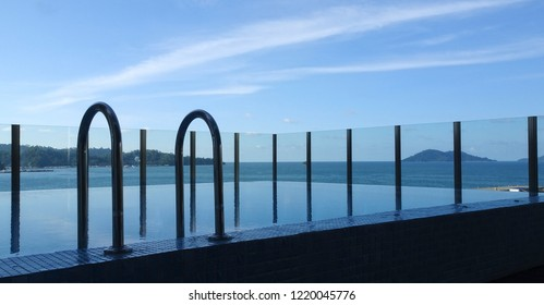 A spa pool surrounded by glass fence with calm water reflecting a blue cloud-streaked later-afternoon sky.