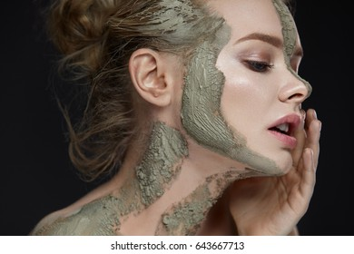 Spa Procedure. Closeup Of Beautiful Young Female Model Applying Cosmetic Mud Facial And Body Mask. Portrait Of Attractive Woman With Makeup And Clay Mask On Her Skin. Beauty Concept. High Resolution