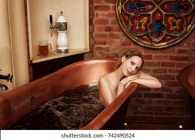 spa procedure - copper bath with dark beer. Beautiful woman bathing with happy smile