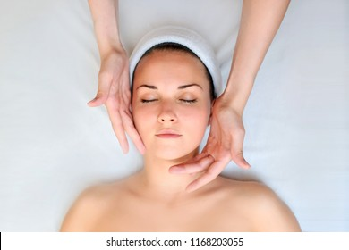 Spa procedure of face massage. Top view. Beautiful young woman lying on back. Masseur /therapist massaging her face