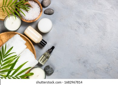 Spa product composition. Sea salt, ccosmetics, towel and tropical leaves at stone table. Top view with copy space.