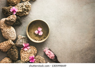 Spa product - facial tonic. Bath salt. Dayspa background with flowers and marine stones.  Spa and wellness setting.