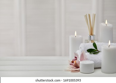 Spa products with aromatic candles, orchid flower and towel on white wooden table. Beauty spa treatment and relax concept. copy space - Shutterstock ID 1691005393