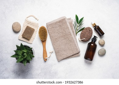 Spa products and cosmetics on white stone background. Natural cosmetics, massage brushes, towel and green plants for spa, home relaxation