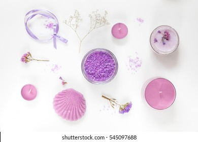 Spa products. Lavender bath salts, dry flowers, soap, cosmetic cream and candles. Violet purple concept. Flat lay on white background, top view.