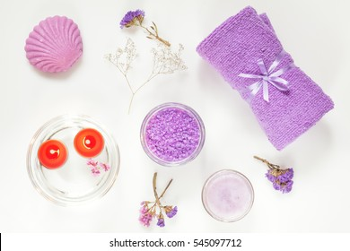 Spa products. Lavender bath salts, dry flowers, soap, cosmetic cream, light candles and towel. Violet purple concept. Flat lay on white background, top view.