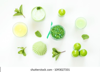 Spa products. Mint bath salts, fresh herbs, soap, cosmetic cream, candles and towel. Green color concept. Flat lay on white background, top view.