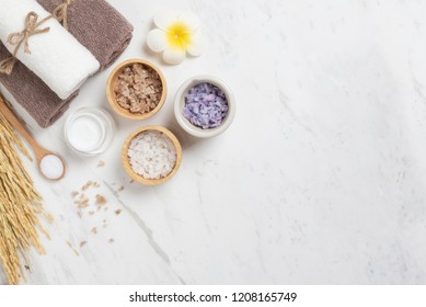 Spa products on white marble background. Salt in Bowl, towels, barley, wooden spoon, towels, plumeria flower with Copy space.