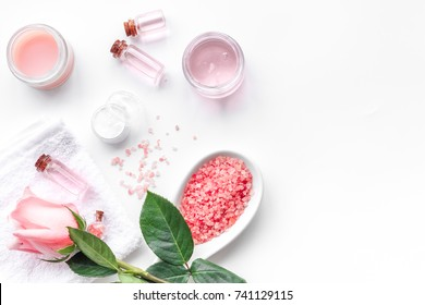 Spa products with rose oil. Cream, lotion and salt on white background top view copyspace