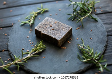 Spa products with soap. oil bottle. Black soap. A bottle of frankincense essential oil. Block of natural carbon soap and a pile of coal on black wood table background