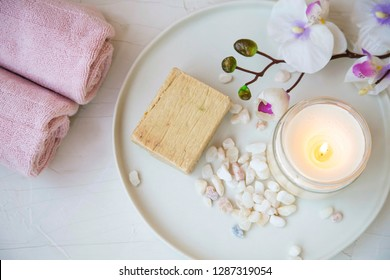 Spa products still life, top view of scented candle, natural soap and cotton towels, spa and wellness background