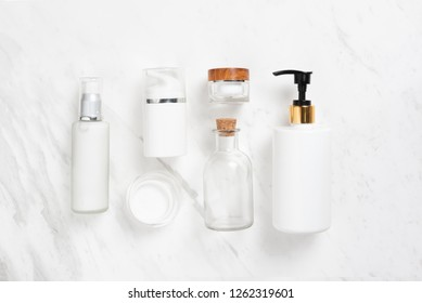 Spa products. Top view of Cosmetic bottles on white marble background. Copy space.