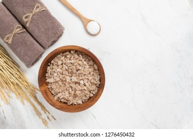 Spa products. Top view of salts in wooden tray in round shape with towels, wooden spoon and ears of barley on white marble background. Copy space.