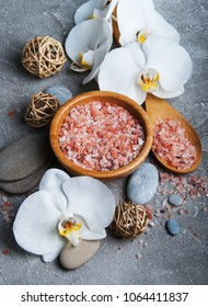 Spa products with white orchids on a gray stone background