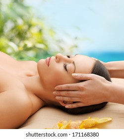 spa, resort and beauty concept - calm beautiful woman in massage salon