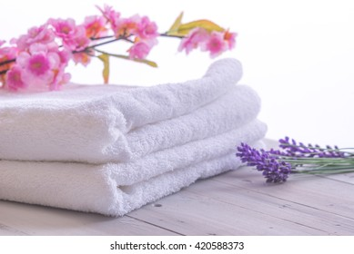 Spa resort, health and beauty concept. Towels and flowers against a white background.