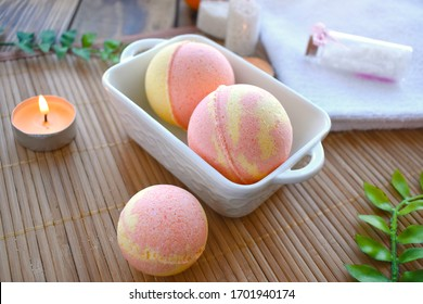 Spa resort setting. Still life image with bath bombs and candle on wooden background. Spring or summer relax concept.