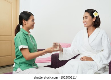 Spa salon administrator offering a glass of fresh water to client