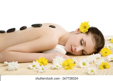 Spa salon: beautiful young woman lying down on the straw mat with flowers and stones. Eyes closed