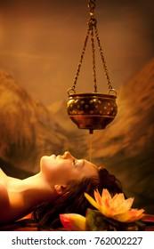 Spa salon: Beautiful Young Woman having Shirodhara - Ayurveda Oil Massage in India Spa Salon with Lotus