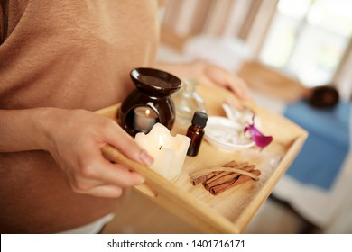 Spa salon worker carrying tray with aroma lamp, candes and essential oils