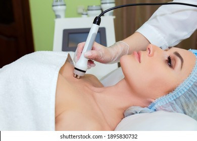 The spa salon's cosmetologist performs a RF lifting procedure on the neckline of a young woman.