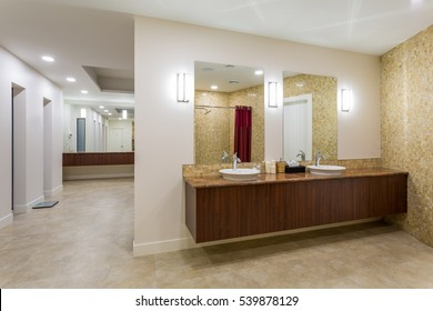 Spa or sauna modern bathroom with shower, white sinks and stone counter top.