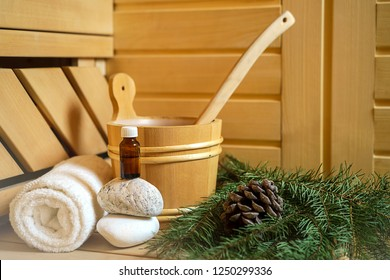 Spa, sauna and wellness setting with water bucket, oil essence, cones, Christmas tree branches, white towel on wooden background. winter wellness concept relax and treatment therapy. Selective focus
