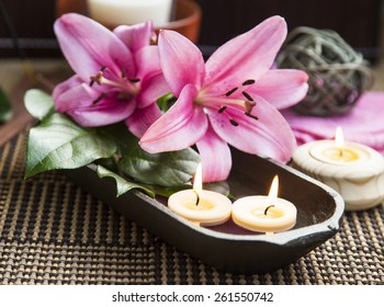 Spa Scene with Pink Lilies and Wooden Water Bowl, Burning Candles and Bamboo Background