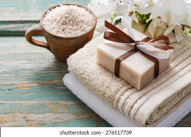 Spa set: bar of handmade natural soap lying on the towels, cup of sea salt and alstroemeria flowers