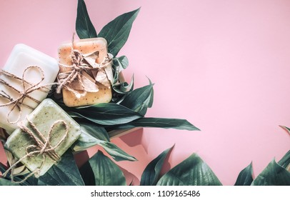 Spa set natural soap in a wooden box with natural foliage on a pink background, the concept of beauty and health
