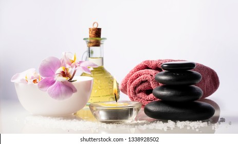 Spa set on white background with bottle of oil, salt, candle, orchid, towel and zen spa stones. With space for text.