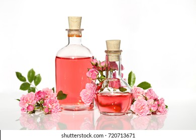 Spa set with rose. rose petals oil , Perfumed Rose Water in glass bottles small pink roses with leaves . Massage, aromatherapy and organic cosmetics concept