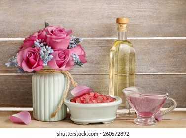 Spa set: sea salt, liquid soap and bottle of essential oil. Bouquet of pink roses and blue muscari flower (Grape Hyacinth).