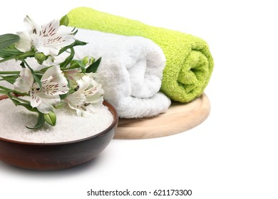 Spa set: sea salt, towel and beautiful flowers isolated on white background