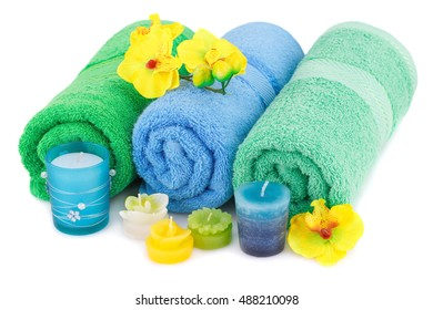 Spa set with towels, candles and flowers isolated on white background.