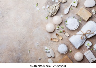 Spa setting from body care and beauty treatment products with flowers on stone background top view. Healthy and wellness concept. Flat lay style.