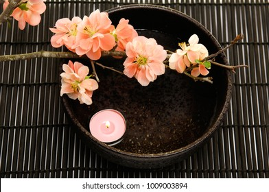 Spa setting with candle ,cherry in bowl on mat