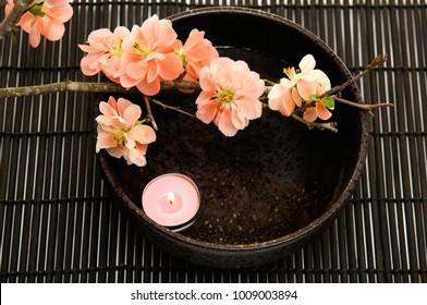 Spa-Bereich mit Kerze, Kirsche in Schüssel auf Matte