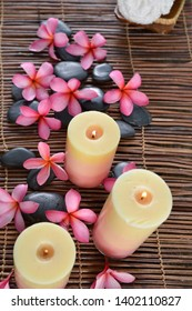 Spa setting with candle frangipani, plumeria ,black stones,towel in basket on mat
