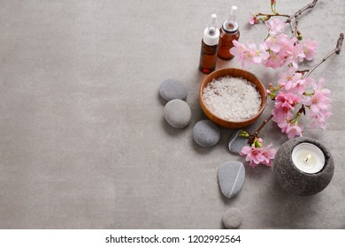 spa setting with cherry flowers,.,candle ,gray stones,bottle oil ,salt in bowl on gray background