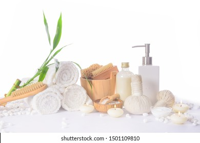 spa setting concept with bath set,oil bottle ,salt in,bowl, pile of white stones and bamboo leaves, herbal ball, spoon,