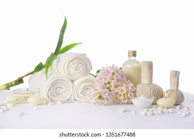spa setting concept with oil bottle ,salt in,bowl, white stones and orchid , herbal ball,, rolled towel,bamboo leaves