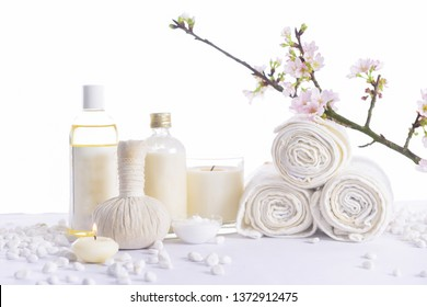 spa setting concept with oil bottle ,salt in,bowl, white stones and cherry flower, herbal ball, rolled towel