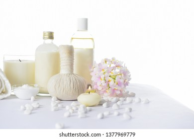 spa setting concept with oil bottle ,salt in,bowl, white stones and orchid , herbal ball,, rolled towel