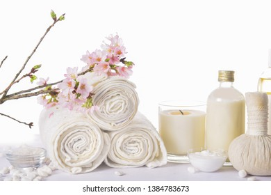 spa setting concept with oil bottle ,salt in,bowl, white stones and cherry flower, herbal ball,, rolled towel