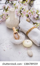 spa setting concept with, lying on cherry, herbal ball,,stones,pile of ,spoon ,salt in bowl ,candl,petals