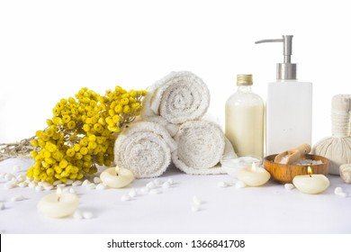 Spa setting with daisy flower with salt in spoon in bowl,candle, herbal ball ,bottle oil ,stones, brush,rolled towel